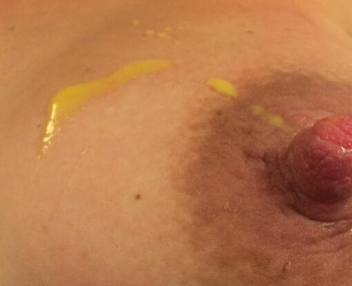 Råmælk på brystet af en kvinde der ligger på ryggen