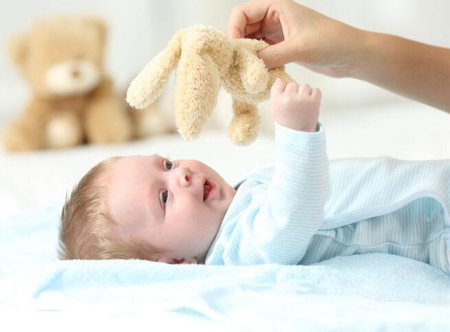 Baby i blåt tøj leger med mor