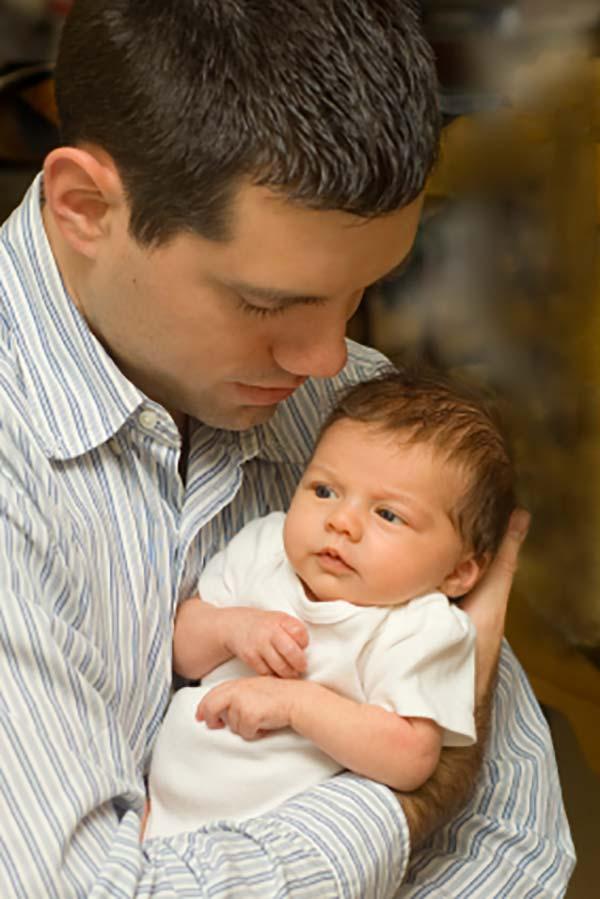 Far kan meget mere end at skifte ble, her holder han baby tæt ind til sig i sine arme