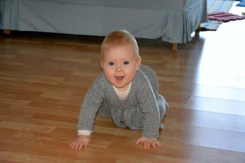 Lille Emma kravler med stort smil på gulvet.
