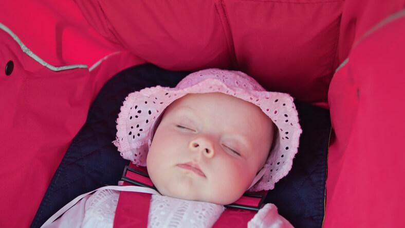 Baby der sover i barnevognen om sommeren