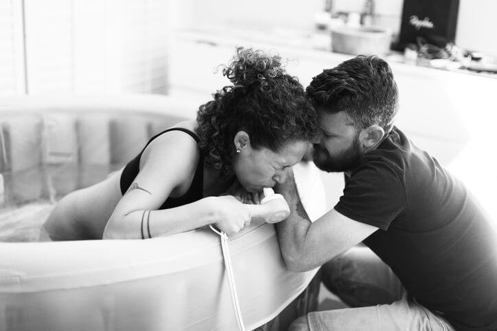 Kvinde ligger i badekar og er langt i fødsel, hjulpet af sin mand